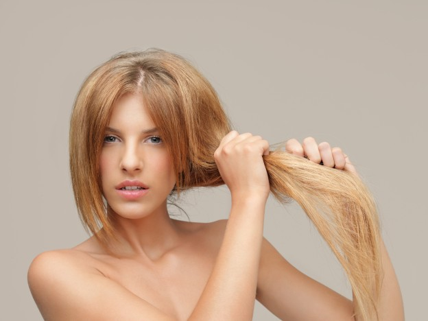 upset woman pulling dry hair split ends